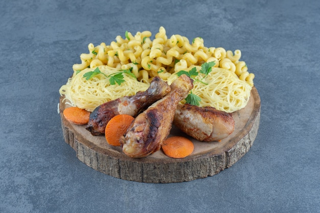 Gambe fritte, maccheroni e spaghetti su un pezzo di legno.