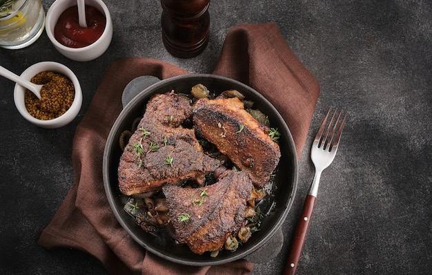 鍋に揚げた肝臓と玉ねぎ、マスタードとケチャップ、暗いテーブル、上面図。
