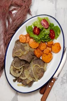 タマネギ、サツマイモ、白い皿にサラダと揚げ肝