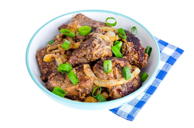 Fried liver with onions in bowl on white.
