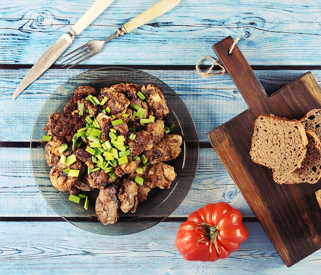Fried liver with onions on a plate, tomato and rye bread