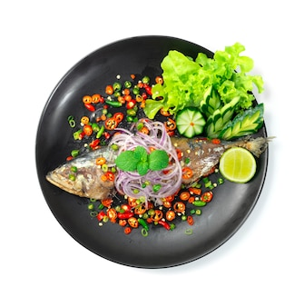 Fried mackerel fish salad with chilli,onion,lime decorate carved vegetable thaifood local style topview