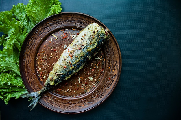 Fried mackerel on a plate. dark background top view.