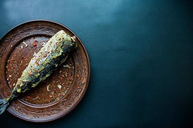 Fried mackerel on a plate, dark background.