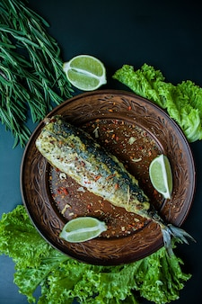 Fried mackerel on a plate with seasonings for fish and greens. dark background top view.