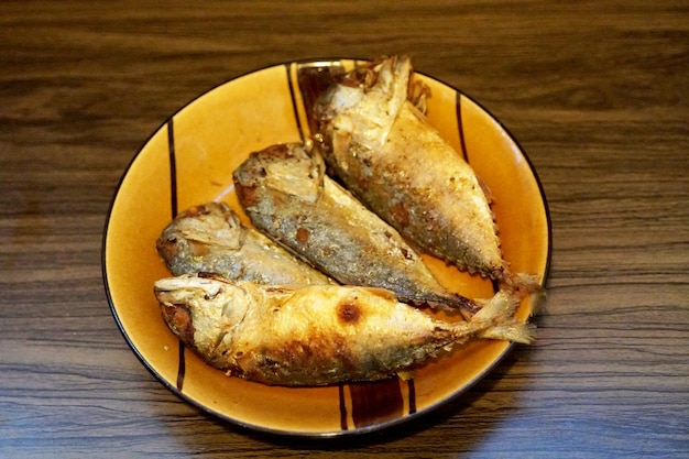 Fried mackerel in the plate on wooden table