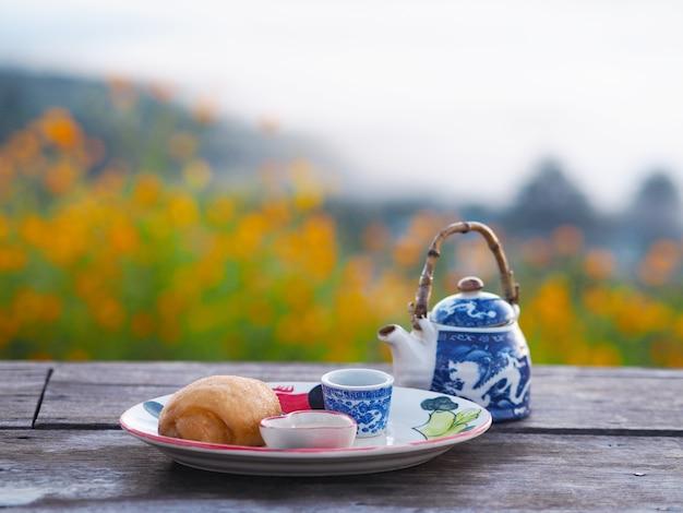 屋外の木製テーブルに練乳と中国茶を添えた揚げ饅頭