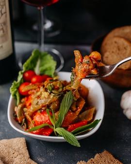 Жареное мясо вместе с жареными овощами красочно нарезанный внутри белой тарелке вместе с буханками красного вина на сером