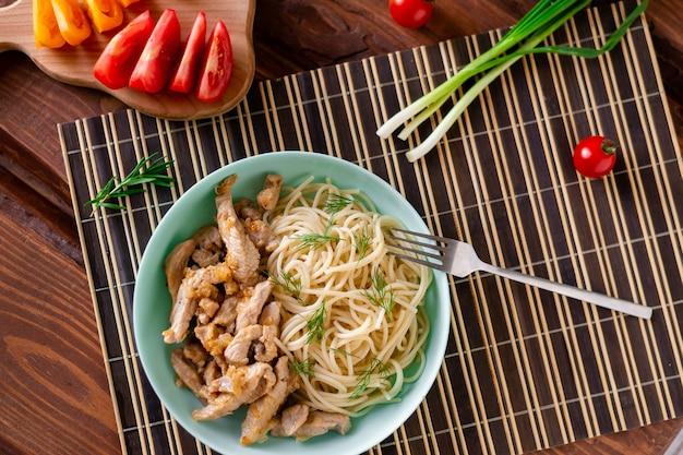 토마토와 허브와 함께 나무 배경에 접시에 튀긴 고기와 스파게티.