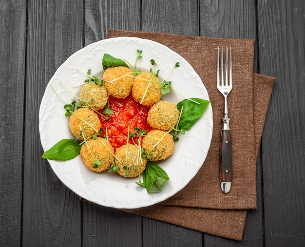 Fried meat balls with vegetables and sauce on plate
