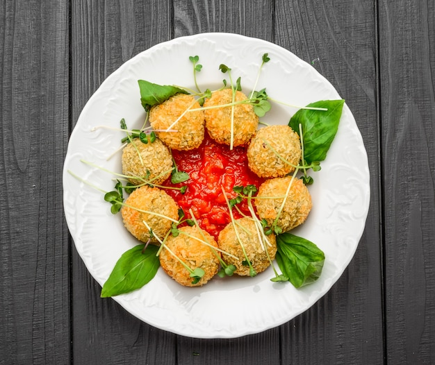 Fried meat balls with vegetables and sauce on a plate