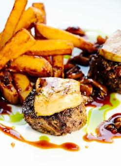 소스에 튀긴 potatoe와 튀긴 고기 돈까스