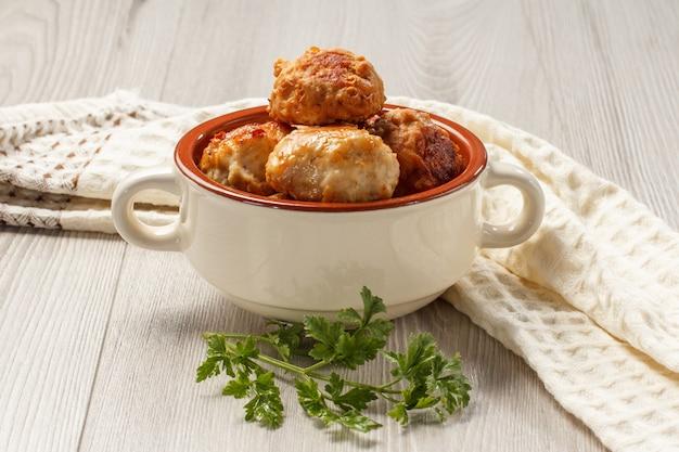 Жареные мясные котлеты в белой керамической суповой миске, ветка свежей петрушки и кухонное полотенце на сером деревянном столе