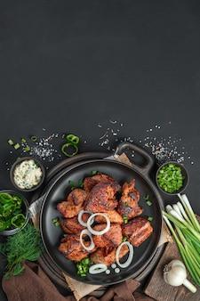 Жареное мясо в черной тарелке на темном фоне с зеленью. вертикальный вид, место для копирования.