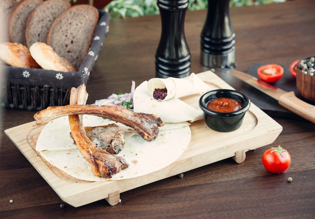 Fried meat kebab with lavash on wooden board