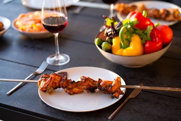꼬치에 튀긴 고기 접시에 케밥 케밥과 와인 한 잔을 곁들인 꼬치 저녁식사여름