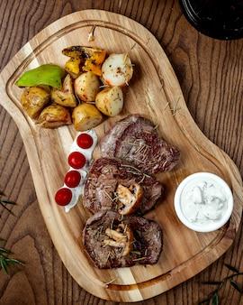 목 판에 야채와 튀긴 고기 스테이크