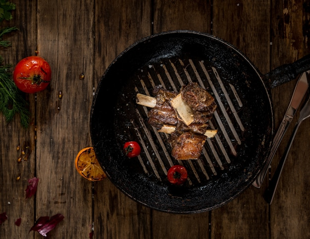 Fried meat with bone in the pan on wooden background, top view