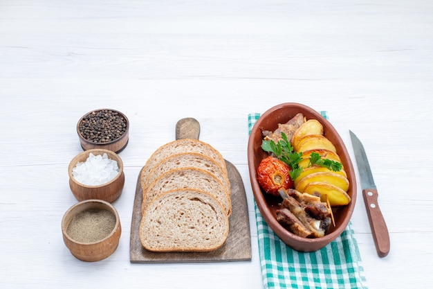 Carne fritta con verdure e prugne al forno all'interno del piatto con pagnotte di pane sale sulla scrivania bianca, cibo pasto carne piatto cena verdura
