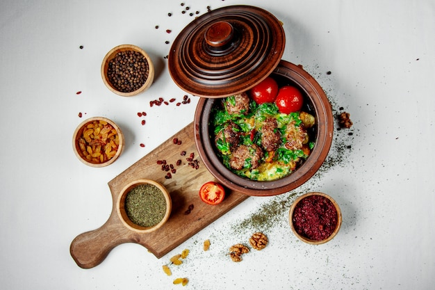 Fried meat with greens and tomatoes in a clay pot
