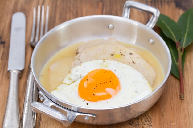 Fried meat with sauce and fried egg in dish on brown wood