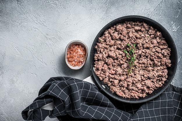 Жареный фарш из говядины и баранины на сковороде с зеленью