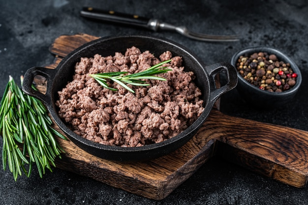 Fried mince beef meat in a pan for cooking pasta. black background. top view.