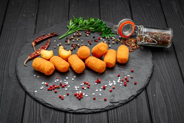Fried mozzarella, cheddar cheese bites, balls with ketchup on rustic stone board