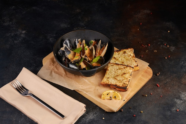 Fried mussels with bread slice, dark background