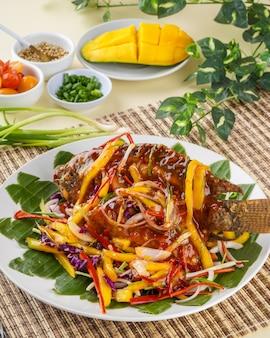 ナイルティラピアまたはイカンニラの揚げ物とマンゴーソースのインドネシア料理と料理のプレートを竹のトレイに乗せて