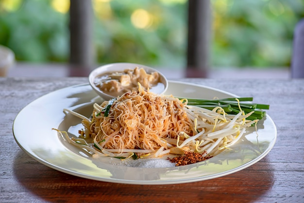 Fried noodle with spring onion and bean sprouts on white plate with garnish.