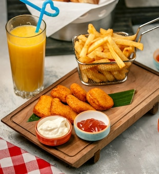 Fried nuggets and french fries on wooden board