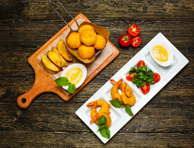 Fried nuggets and potatoes with sliced eggs and tomatoes