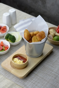 Fried nuggets in a silver bucket on the table