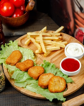Fried nuggets with french fries on wooden board