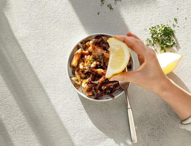 Жареные кусочки осьминога с лимоном, мякотью фри, резким прямым солнечным светом