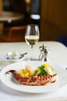 Жареные щупальца осьминога с брокколи и цветной капустой на белой тарелке с белым вином