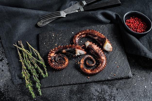 Жареные щупальца осьминога с тимьяном и розовым перцем. свежие морепродукты