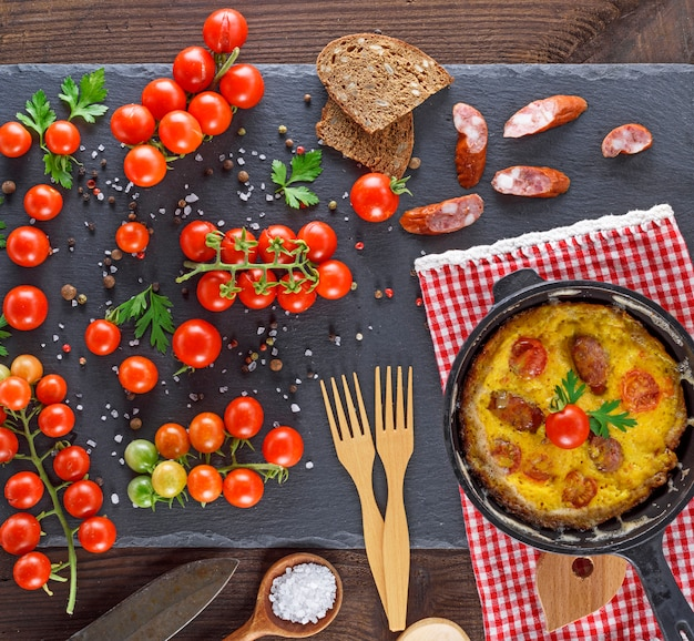 Fried omelette from chicken eggs with red cherry tomatoes