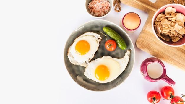 Жареный омлет с помидорами и огурцом на тарелке на белом фоне
