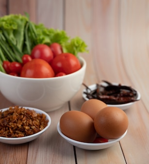 Жареный лук, перец, яйца, помидоры, салат и зеленый лук в белой чашке на деревянном полу.