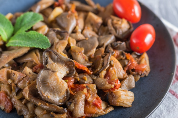 Fried oyster mushrooms with tomatoes on gray concrete background