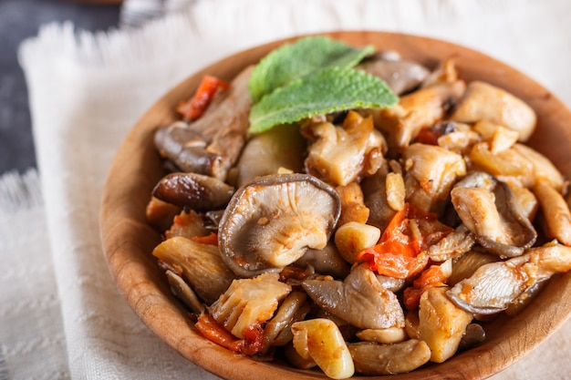 Fried oyster mushrooms with tomatoes in wooden plate on black concrete background