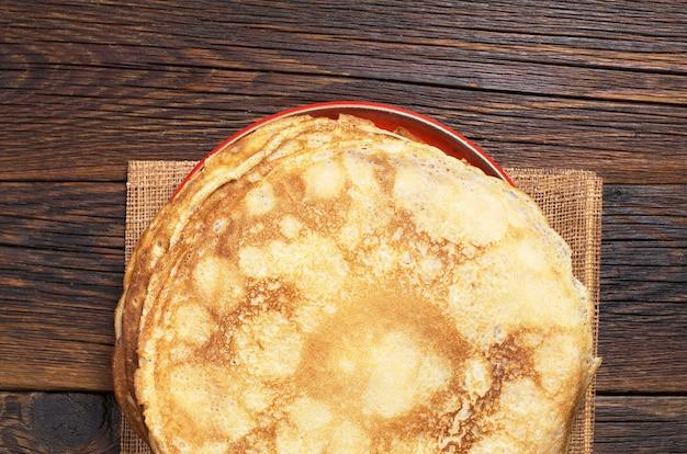 暗い木製のテーブル、上面図のプレートで揚げたパンケーキ