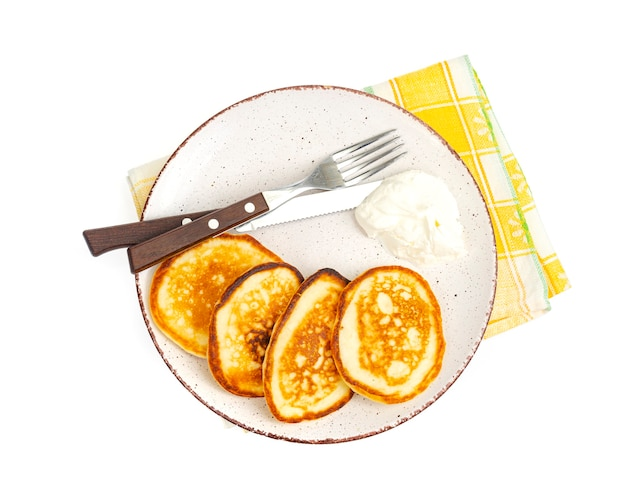 Fried pancakes with sour cream, fork and knife on plate, colored napkin