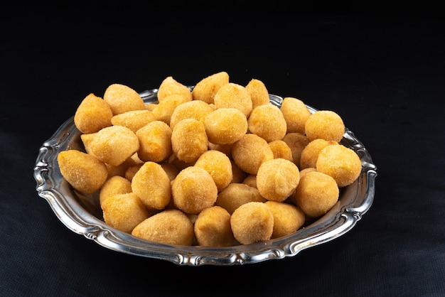 Fried party snacks arranged on a stainless steel plate with black background. top view