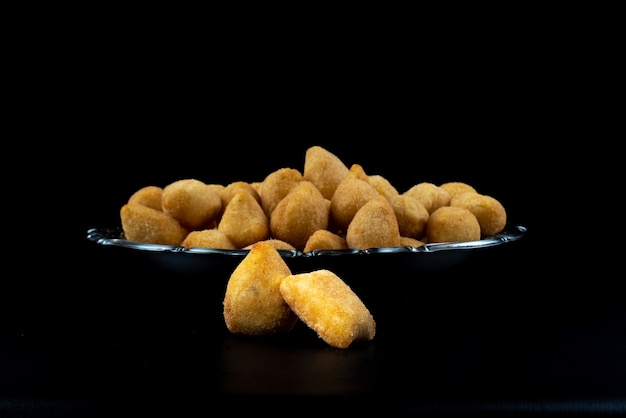 Fried party snacks arranged on a stainless steel plate with black background