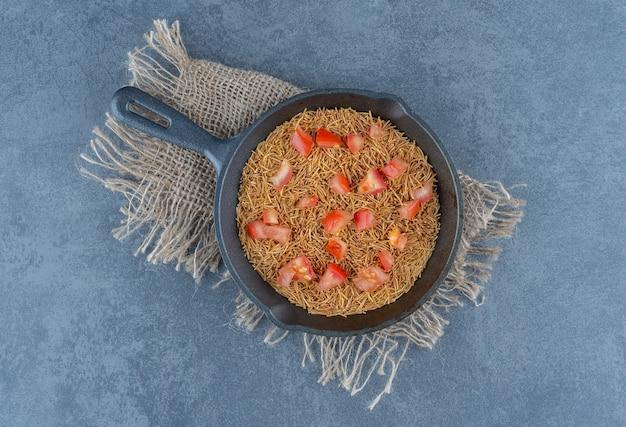 Жареные макароны с ломтиками помидоров на черной сковороде.