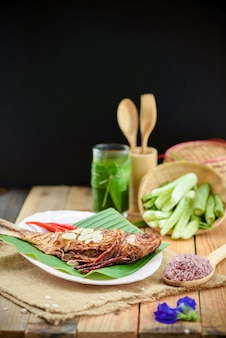 Fried pickled fish with side dishes on wooden desk and black background