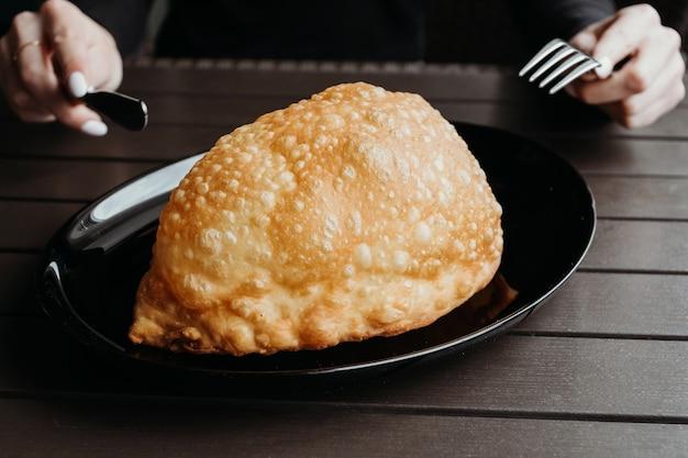 Жареный пирог с мясом и луком на черной тарелке на деревянном столе и руках, держащих вилку и нож